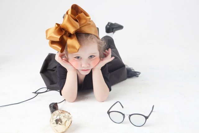 眼鏡を前にうつ伏せで両肘をつき顎をのせている小さな女の子