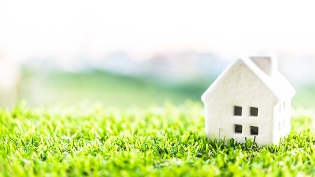 芝生の上に建つ白い一軒家の模型