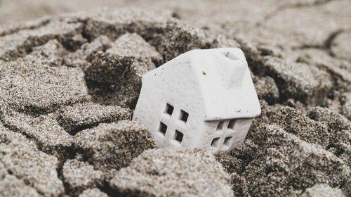 地盤沈下で埋もれた白い家のミニチュア
