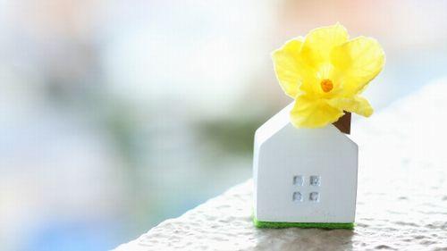 煙突に黄色い花を挿した白い家のミニチュア