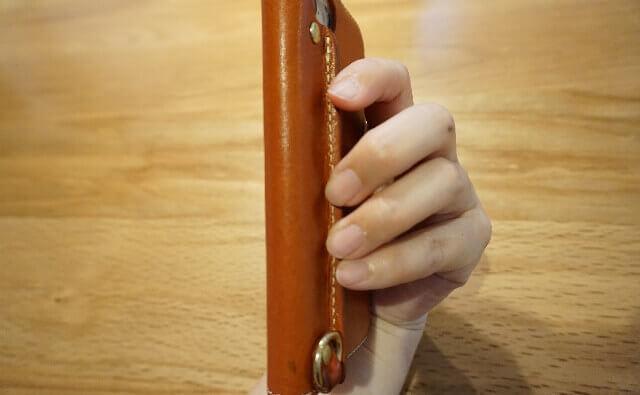 HUKUROスマホケースのバックグリップに指をかけて持つ
